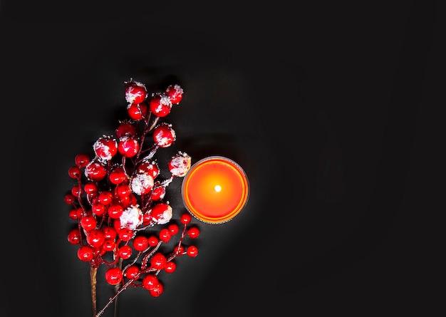 Świąteczna kompozycja świąteczna lub noworoczna z czerwonymi jagodami ostrokrzewu w śniegu i płonącą świecą woskową.