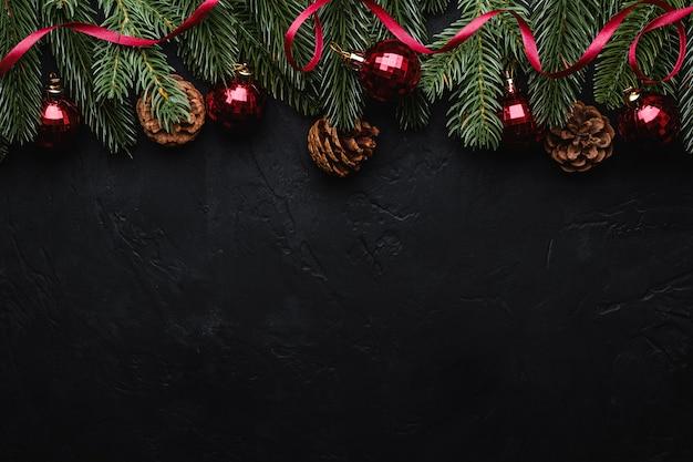 Świąteczna kompozycja świąteczna z czerwoną wstążką, dekoracjami ozdobnymi i bombkami, szyszkami jodły i sosny