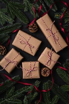 Świąteczna kompozycja świąteczna z czerwoną wstążką, ekologicznymi pudełkami na prezenty, szyszkami i jodłą