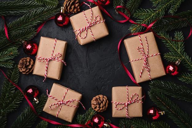 Świąteczna kompozycja świąteczna z czerwoną wstążką, ozdobami i bombkami oraz ekologicznymi pudełkami na prezenty
