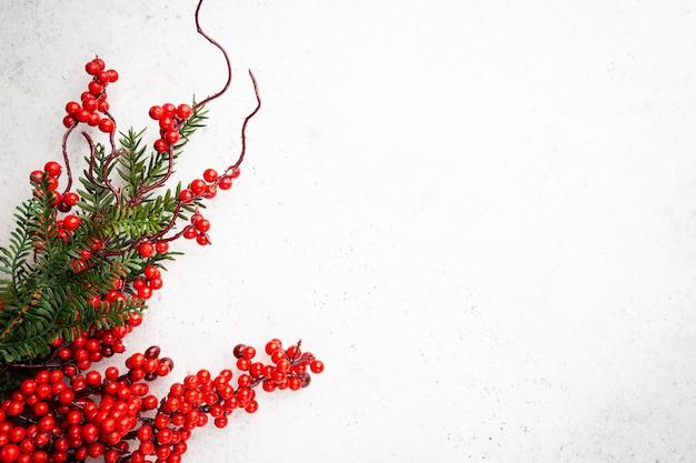 Świąteczna kompozycja świąteczna z ozdobami świątecznymi czerwonymi jagodami rozgałęzia się na białym tle