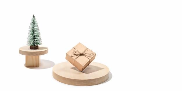 Świąteczna kompozycja świąteczna z ozdobną choinką i jednym pudełkiem na prezent diy na drewnianych podium na białym tle. modny nowoczesny minimalizm i równowaga. świąteczna kartka z życzeniami. skopiuj miejsce. transparent.