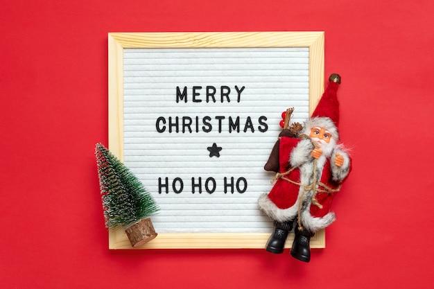 Świąteczna kompozycja świętego mikołaja, drzewo, biała płyta pilśniowa na czerwonym tle