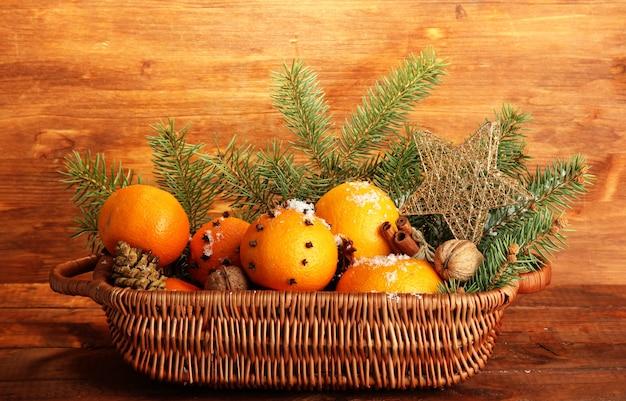 Świąteczna kompozycja w koszu z pomarańczami i jodłą, na drewnianym tle
