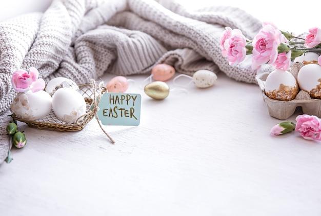 Świąteczna kompozycja wielkanocna z jajkami, kwiatami i napisem happy easter kopia miejsce