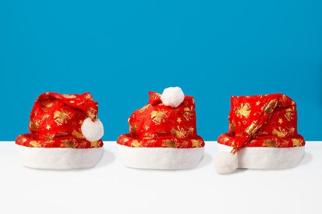 Świąteczna kompozycja wykonana z czapek świętego mikołaja na podwójnym niebieskim i białym tle, widok z przodu, tło boże narodzenie