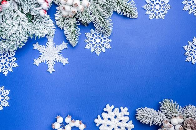 Świąteczna kompozycja z białymi dekoracjami świątecznymi i gałęziami jodły na niebieskim plecach