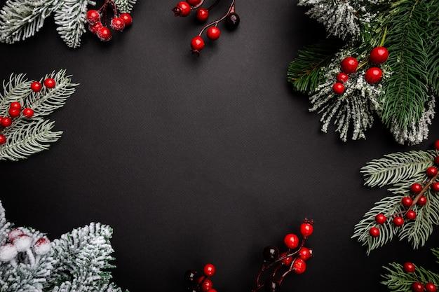 Świąteczna kompozycja z czerwonymi jagodami i gałęziami jodły na czarnym tle