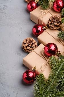 Świąteczna kompozycja z czerwonymi ornamentami i bombkami, jodłą, prezentami i szyszkami