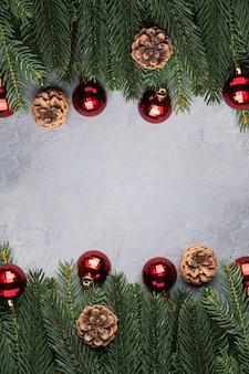 Świąteczna kompozycja z czerwonymi ornamentami i bombkami, szyszkami jodły i sosny