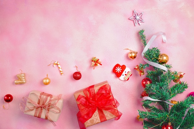 Świąteczna kompozycja z dekoracjami i pudełkiem z kokardkami na różowym pastelowym tle. koncepcja zima, nowy rok. leżał na płasko, widok z góry, miejsce na kopię.