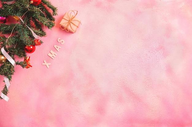 Świąteczna kompozycja z dekoracjami i pudełkiem z kokardkami na różowym pastelu. leżał na płasko