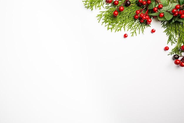 Świąteczna kompozycja z dekoracjami świątecznymi czerwonymi jagodami i gałęziami tui na białym