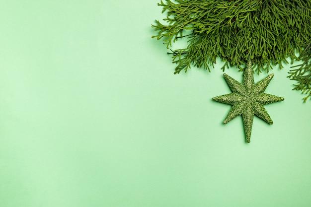 Świąteczna kompozycja z dekoracjami świątecznymi i gałęziami tui na zielonym tle