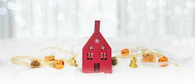 Świąteczna kompozycja z domową czerwienią, prezentami i świątecznymi dekoracjami na łóżku z białym kocem.