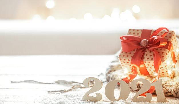 Świąteczna kompozycja z drewnianym nowym rokiem numer 2021 i pudełkiem na kopię w tle.
