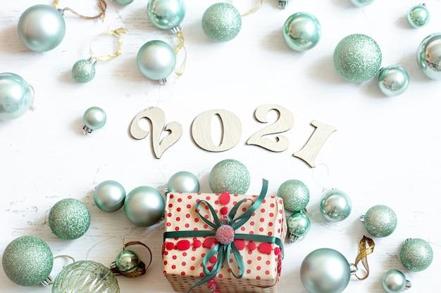Świąteczna kompozycja z drewnianym numerem na nadchodzący rok i niebieskie bombki z pudełkiem na białym tle.