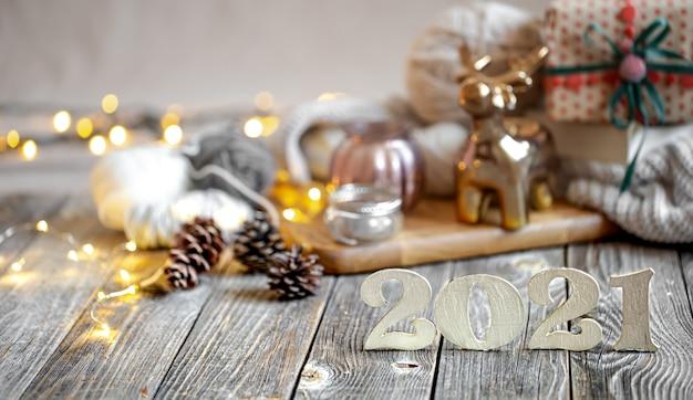 Świąteczna kompozycja z drewnianym numerem na nadchodzący rok na tle detali dekoracyjnych.