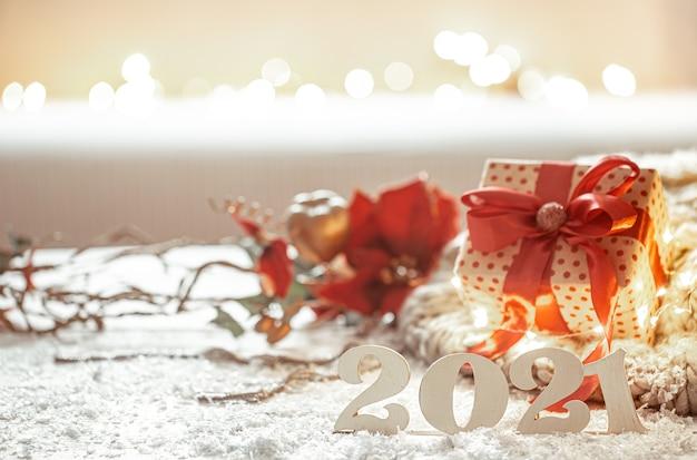 Świąteczna kompozycja z drewnianymi numerami noworocznymi i detalami wystroju na rozmytym tle.