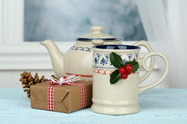 Świąteczna kompozycja z filiżanką i czajnikiem gorącego napoju, na drewnianym stole
