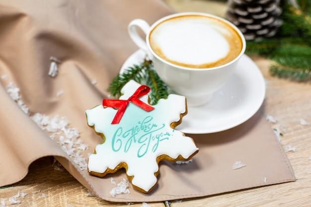 Świąteczna kompozycja z filiżanką kawy, sosną, gałązką jodły i piernikiem