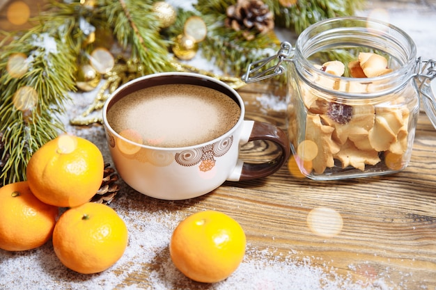 Świąteczna kompozycja z gałązką jodły, ciasteczkami, filiżanką kawy i mandarynkami
