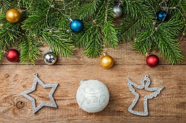 Świąteczna kompozycja z gałęzi jodły i ozdób choinkowych na drewnianym tle widok z góry z miejsca na kopię