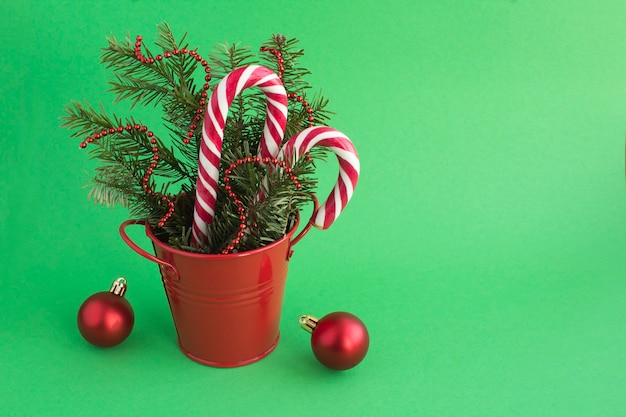 Świąteczna kompozycja z gałęzi świerkowych w czerwonym wiadrze na zielonym tle. skopiuj miejsce.