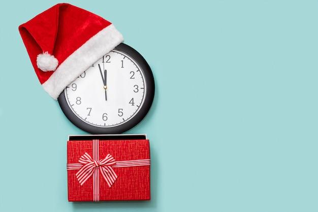 Świąteczna kompozycja z klasycznym zegarem analogowym w czerwonej czapce i czerwonym pudełku z kokardą na białym tle
