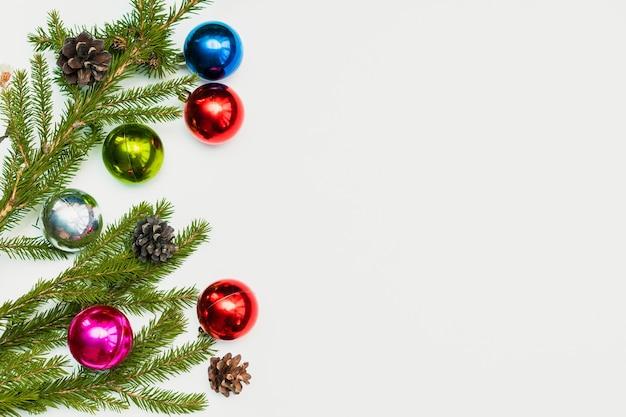 Świąteczna kompozycja z kolorowymi kulkami, szyszkami i gałęziami jodły. ornament, dekoracje sylwestrowe na białym tle. szablon karty pozdrowienia makieta z miejsca na kopię, płasko, widok z góry.