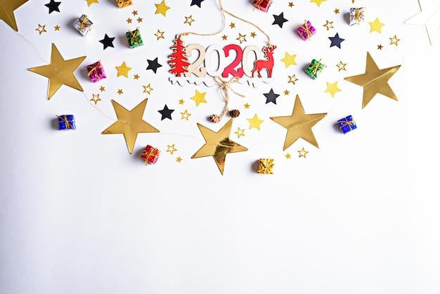 Świąteczna kompozycja z kolorowymi pudełeczkami na prezenty, złote gwiazdki, płaski układ