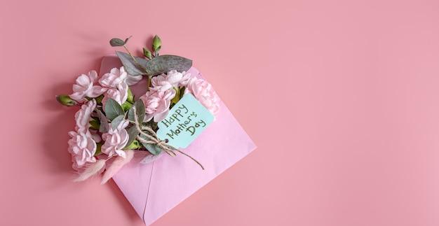 Świąteczna kompozycja z kopertą ze świeżymi kwiatami i napisem happy mother's day flat lay.