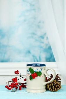 Świąteczna kompozycja z kubkiem gorącego napoju, na drewnianym stole