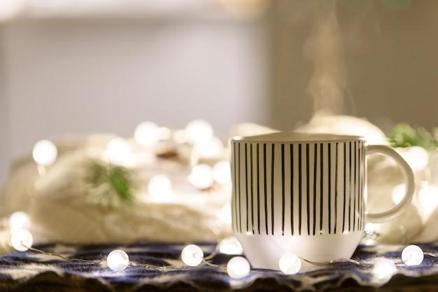 Świąteczna kompozycja z kubkiem gorącego napoju, świecąca girlanda, biały sweter na powierzchni, kopia przestrzeń. przytulny dom.