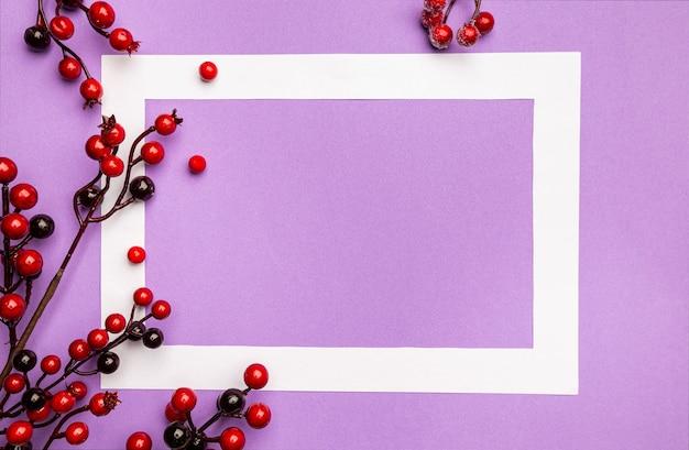 Świąteczna kompozycja z ozdobami świątecznymi czerwonymi jagodami i białą ramką