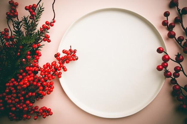 Świąteczna kompozycja z ozdobami świątecznymi czerwonymi jagodami i białym talerzem