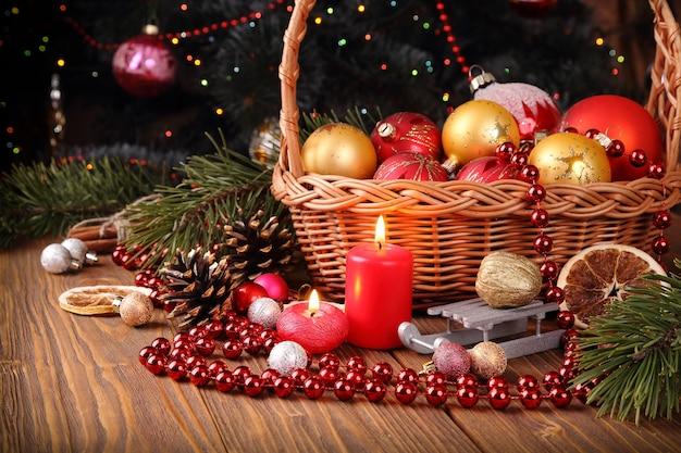Świąteczna kompozycja z ozdobami świątecznymi i świecami na tle udekorowanej choinki