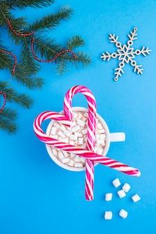 Świąteczna kompozycja z patyczkami karmelu w kształcie serca i gorącą czekoladą z piankami na niebieskim tle. widok z góry.