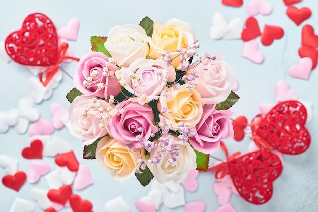 Świąteczna kompozycja z pięknych delikatnych róż w różowym okrągłym pudełku na jasnoniebieskim tle. leżał płasko, kopia przestrzeń. kartka z życzeniami.