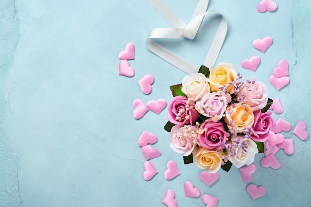 Świąteczna kompozycja z pięknymi delikatnymi kwiatami róż w różowym okrągłym pudełku na jasnoniebieskim tle. mieszkanie świeckich, kopia przestrzeń. kartka z życzeniami.