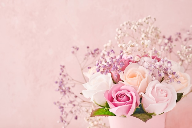 Świąteczna kompozycja z pięknymi delikatnymi kwiatami róż w różowym okrągłym pudełku na jasnoróżowym tle. leżał płasko, kopia przestrzeń. kartka z życzeniami.
