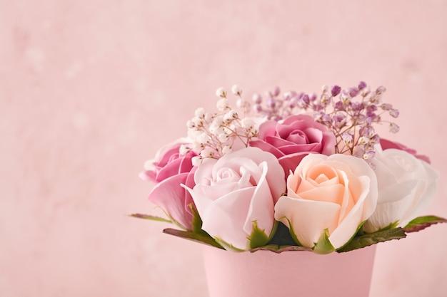 Świąteczna kompozycja z pięknymi delikatnymi kwiatami róż w różowym okrągłym pudełku