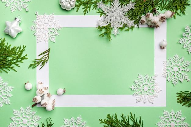Świąteczna kompozycja z płatków śniegu i gałęzi tui na zielonym tle widok z góry