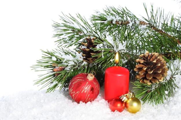 Świąteczna kompozycja z płonącą świeczką i dekoracjami na śniegu
