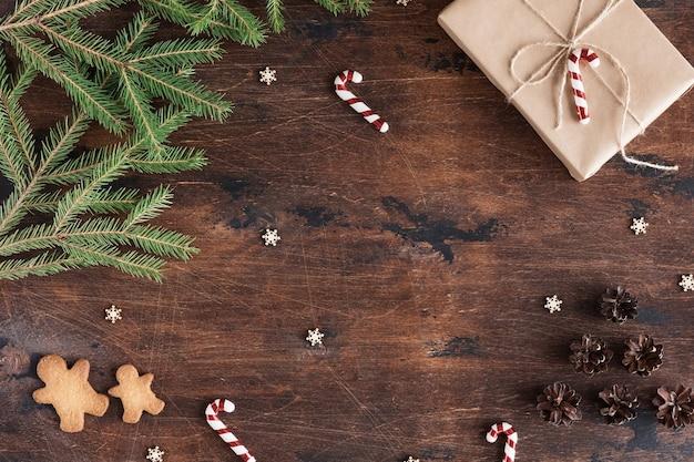 Świąteczna kompozycja z prezentem i piernikowym człowiekiem na drewnianym ciemnym tle z szyszkami, gałęzie jodły na drewnianym biurku, widok płaski i widok z góry, kopia przestrzeń