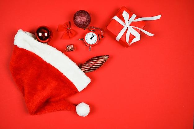 Świąteczna kompozycja z pudełkiem prezentów santa hat czerwone dekoracje na czerwonym tle