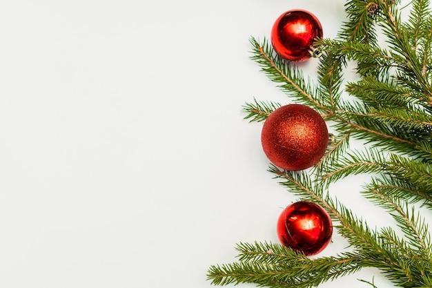 Świąteczna kompozycja z pustą ramą kolorowych czerwonych kulek i gałęzi jodły. ornament, dekoracje sylwestrowe na białym tle. szablon karty z życzeniami makiety z miejscem na kopię, płasko, widok z góry