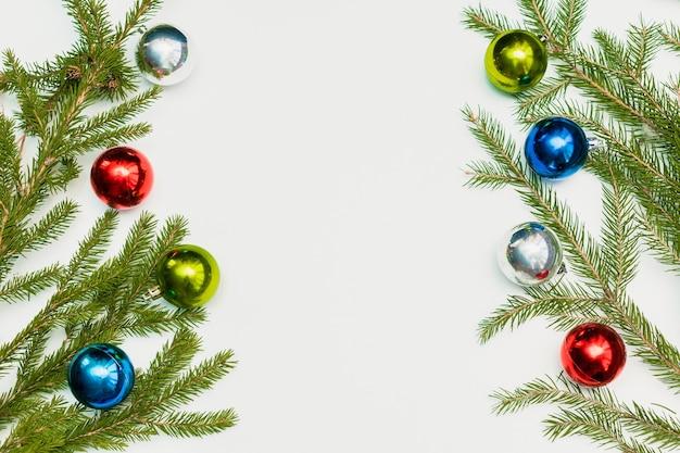 Świąteczna kompozycja z pustą ramą kolorowych kulek i gałęzi jodły. ornament, dekoracje sylwestrowe na białym tle. szablon karty pozdrowienia makieta z miejsca na kopię, płasko, widok z góry.