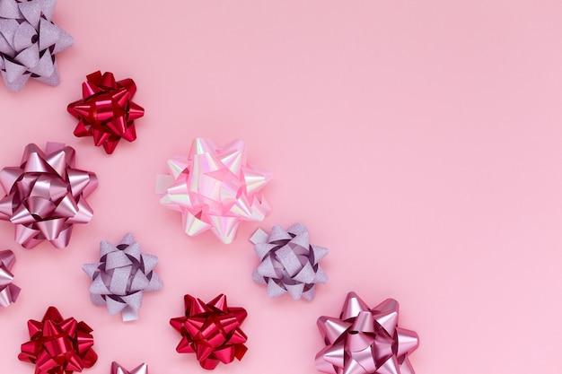 Świąteczna kompozycja z różnymi dekoracjami w postaci różowych kokardek na różowym tle.