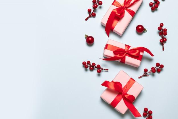 Świąteczna kompozycja z różowymi pudełkami z czerwonymi satynowymi wstążkami
